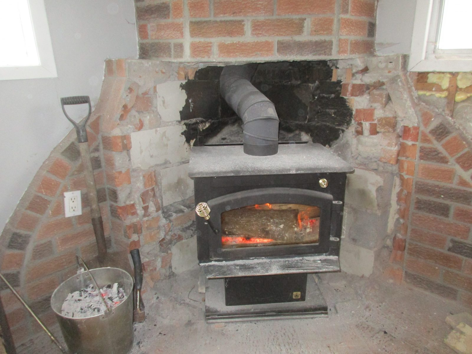 Interesting wood stove installation in old fireplace location.