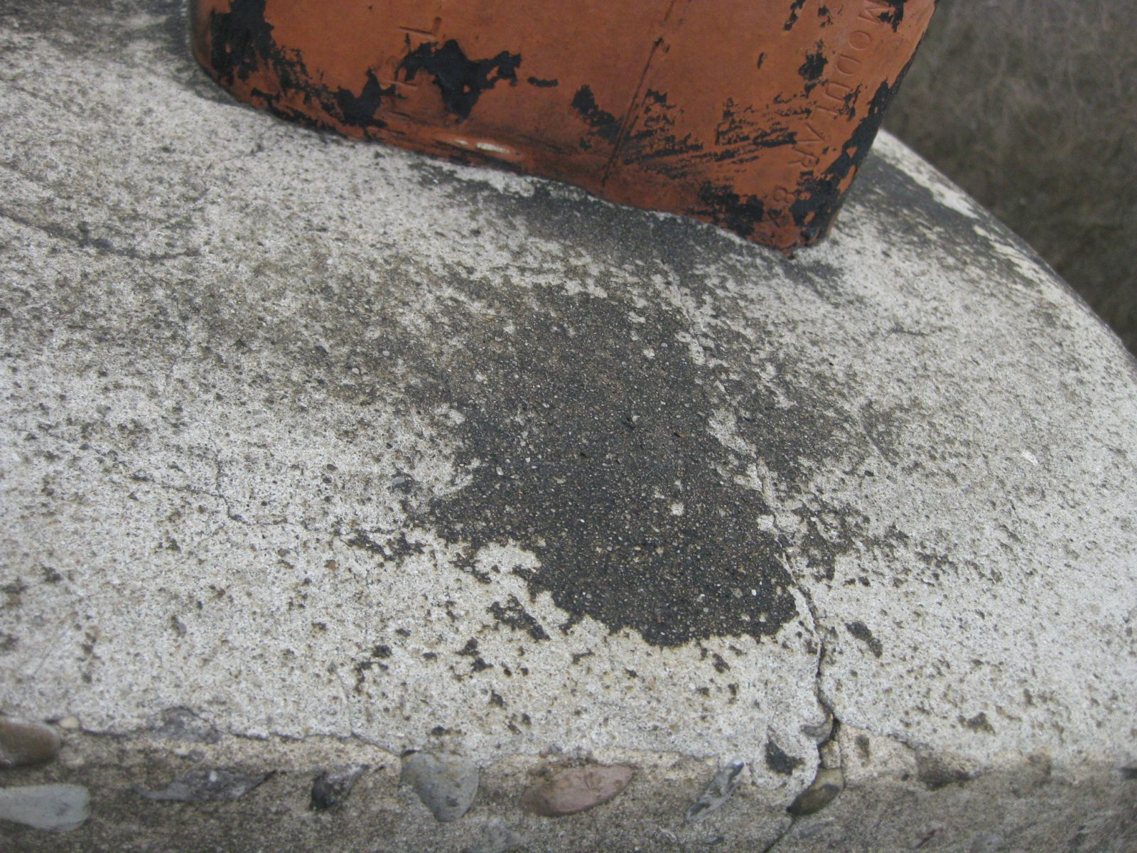 Chimney Cap has crack in masonry and requires sealing.