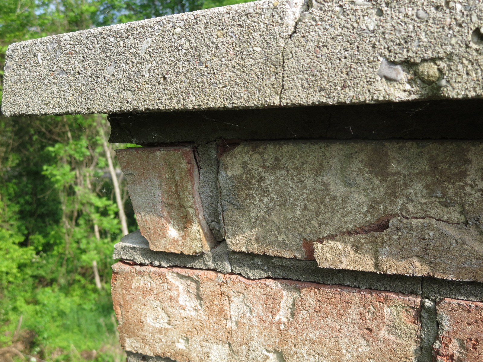 Chimney Cap is cracked and brick mortar loose with spalling brick.