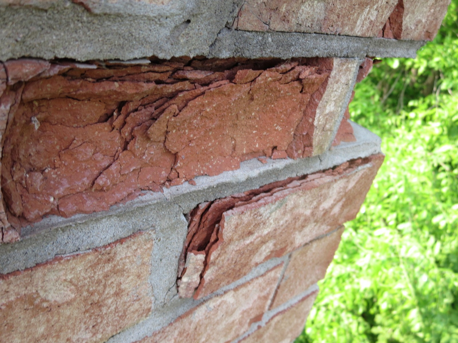 Leaking Cap has caused brick to spall on chimney.  Chimney requires repair.