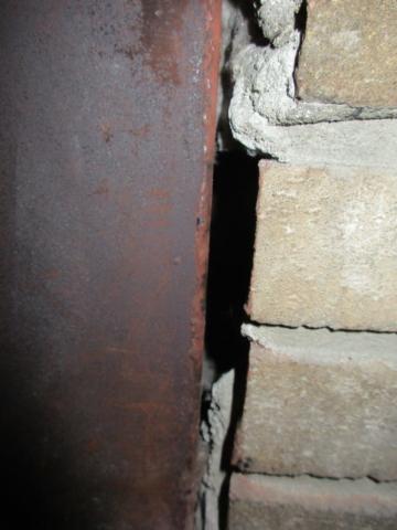 Gaps at firebox and masonry require repair.