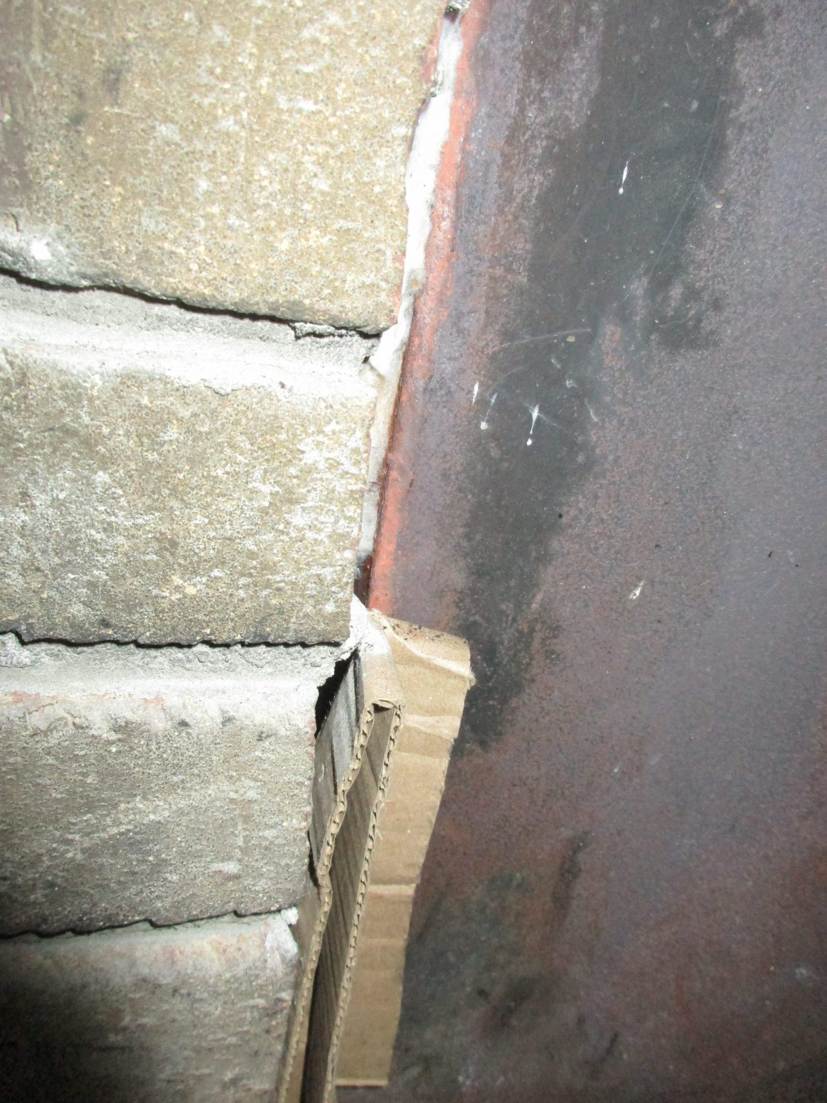 Gaps at firebox sealed with pieces of cardboard